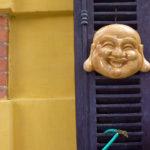 Lachender Buddha neben gelber Hauswand - Strassenszene in Vietnam