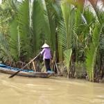Frau im Ruderboot auf einem Nebenkanal im Mekong Delta