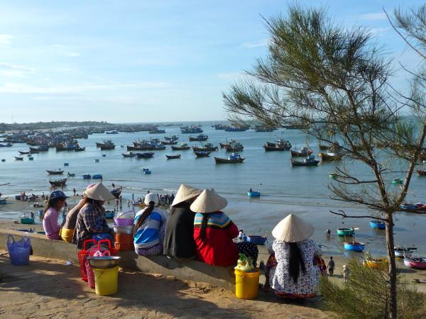 Mehrere vietnamesische Frauen warten auf Ankunft der Fischerboote im Fischerdorf in Mui Ne, Vietnam